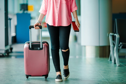 Woman in casual clothing at the airport with a pink suitcase in one hand and a cellphone in the other