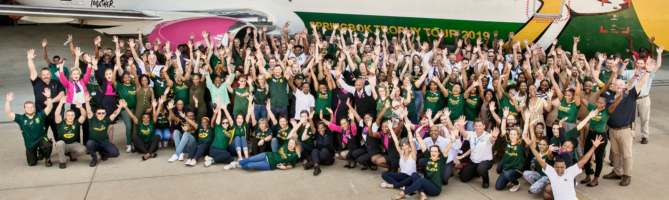 A group of FlySafair staff cheering on the Boks in front of a Springbok branded aircraft